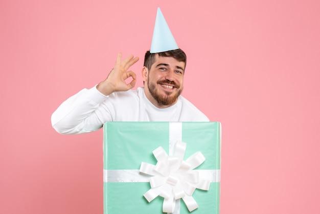 Widok z przodu młody mężczyzna stojący wewnątrz pudełka na różowym zdjęciu kolor emocji świątecznej piżamy