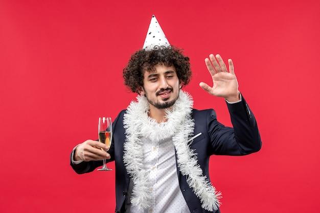 Widok z przodu młody mężczyzna świętuje kolejny rok na czerwonej ścianie wakacje boże narodzenie człowieka