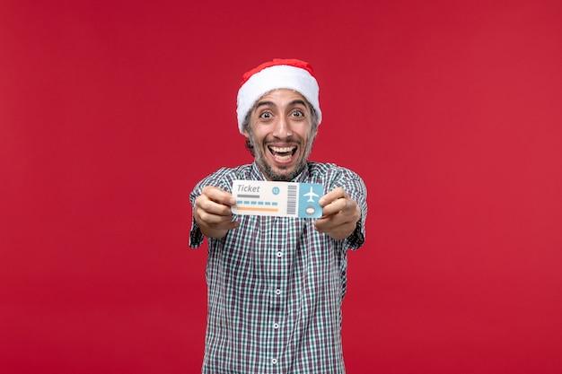 Widok z przodu młody mężczyzna szczęśliwie trzymając bilet na czerwonym tle