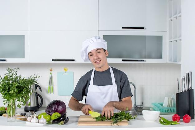 Widok z przodu młody mężczyzna szef kuchni w mundurach do cięcia zieleni