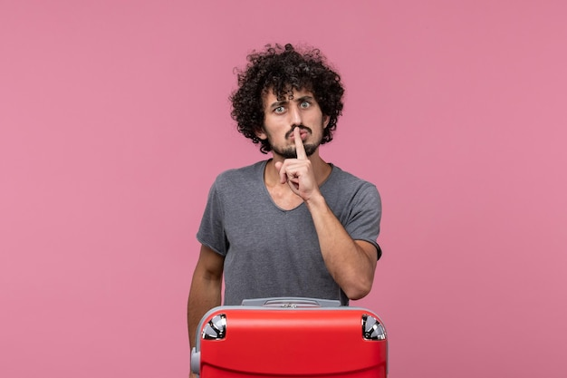 Widok z przodu młody mężczyzna szykuje się na wakacje z pomieszanym wyrazem twarzy na różowej przestrzeni