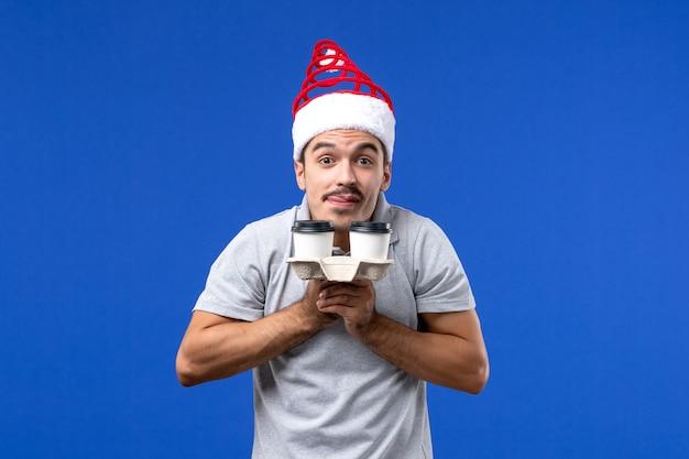 Widok z przodu młody mężczyzna trzyma filiżanki kawy na niebieskiej ścianie emocja mężczyzna nowy rok