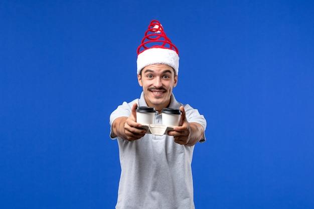 Widok z przodu młody mężczyzna trzyma filiżanki kawy na niebieskiej ścianie emocje mężczyzna nowy rok