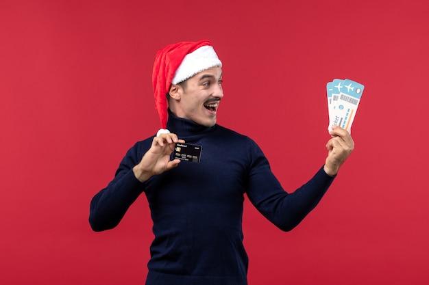 Widok z przodu młody mężczyzna trzyma kartę bankową i bilety na czerwonym tle