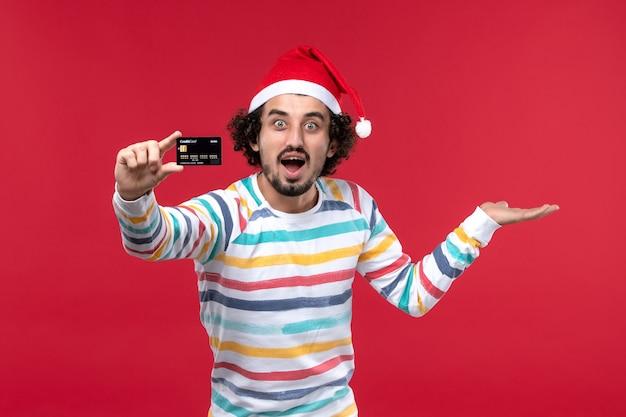 Widok z przodu młody mężczyzna trzyma kartę bankową na czerwonej ścianie emocji czerwonych męskich wakacji