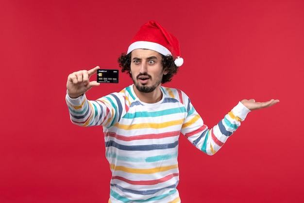 Widok z przodu młody mężczyzna trzyma kartę bankową na czerwonym biurku emocja czerwony mężczyzna wakacje