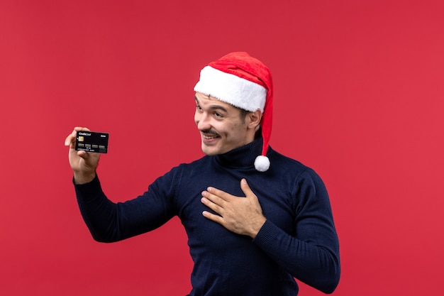 Widok z przodu młody mężczyzna trzyma kartę bankową na czerwonym tle
