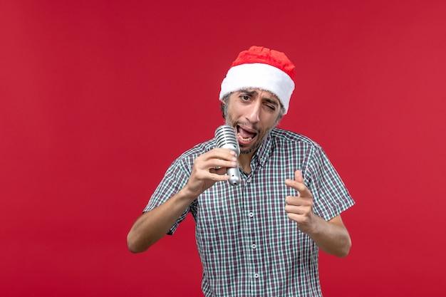 Widok z przodu młody mężczyzna trzyma mikrofon na czerwonym tle
