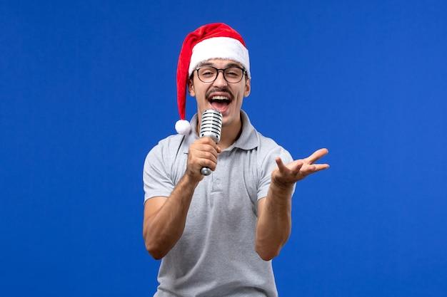 Widok z przodu młody mężczyzna trzyma mikrofon na niebieskiej ścianie mężczyzna muzyka piosenkarka nowego roku