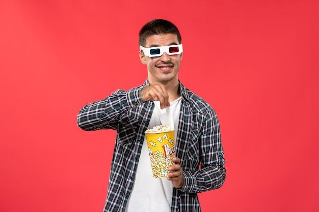 Widok z przodu młody mężczyzna trzyma pakiet popcornu d okulary przeciwsłoneczne na czerwonej ścianie męskie filmy teatr kino film