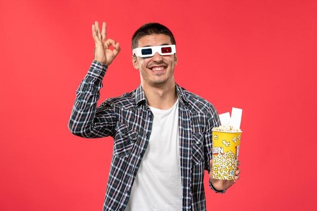Widok z przodu młody mężczyzna trzyma pakiet popcornu i bilety na czerwonej powierzchni kino kino film filmowy