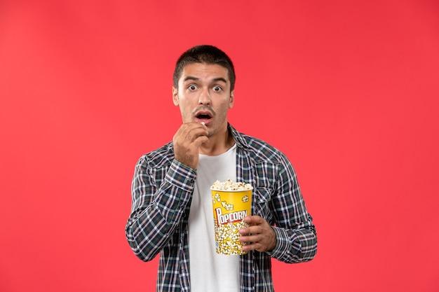 Widok z przodu młody mężczyzna trzyma pakiet popcornu i je na jasnoczerwonej ścianie kino kino męski film