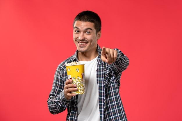 Widok z przodu młody mężczyzna trzyma pakiet popcornu i uśmiecha się na jasnoczerwonej ścianie kino film teatralny chłopiec mężczyzna