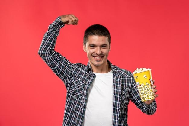 Widok z przodu młody mężczyzna trzyma pakiet popcornu i uśmiecha się zginając na jasnoczerwonej ścianie kino film teatralny chłopiec mężczyzna