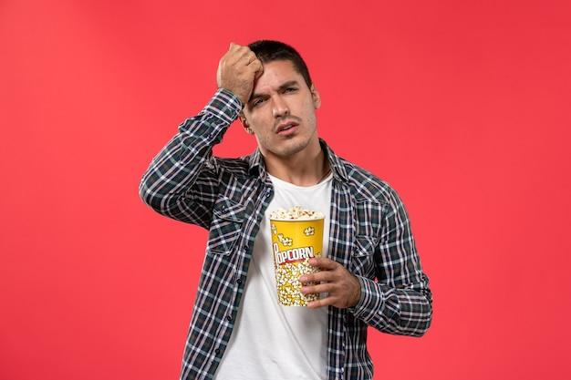 Widok z przodu młody mężczyzna trzyma pakiet popcornu na jasnoczerwonej ścianie kino film teatralny chłopiec mężczyzna