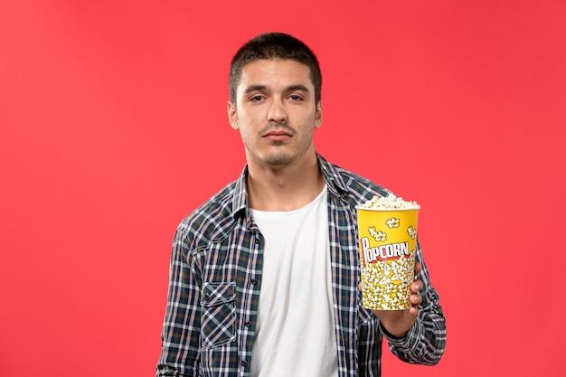 Widok z przodu młody mężczyzna trzyma pakiet popcornu na jasnoczerwonej ścianie kino kino film filmowy