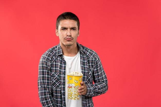 Widok z przodu młody mężczyzna trzyma pakiet popcornu na jasnoczerwonej ścianie kino kino film męski film