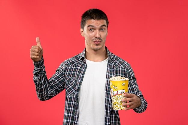 Widok z przodu młody mężczyzna trzyma pakiet popcornu na jasnoczerwonej ścianie kino kino film męski