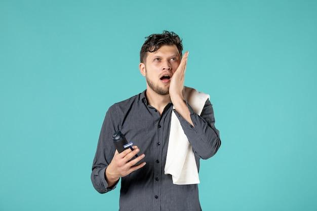 Widok z przodu młody mężczyzna trzyma piankę do golenia i brzytwa na niebieskim tle