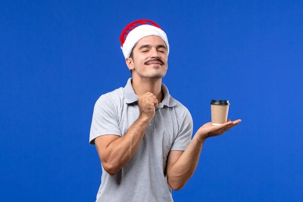 Widok z przodu młody mężczyzna trzyma plastikową filiżankę kawy na niebieskim biurku emocja mężczyzna nowy rok