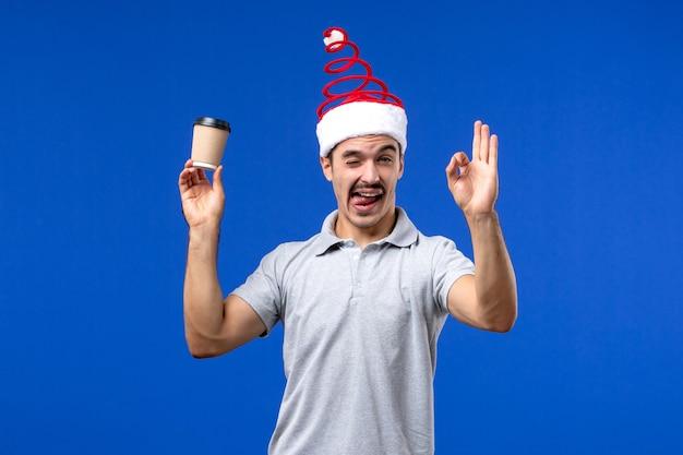 Widok z przodu młody mężczyzna trzyma plastikową filiżankę kawy na niebieskim biurku nowy rok męskie wakacje