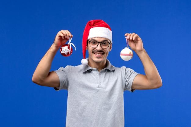 Widok z przodu młody mężczyzna trzyma plastikowe zabawki drzewa na niebieskim tle mężczyzna mężczyzna wakacje nowy rok