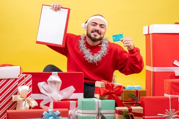 Widok z przodu młody mężczyzna trzyma plik i kartę bankową na żółtym tle