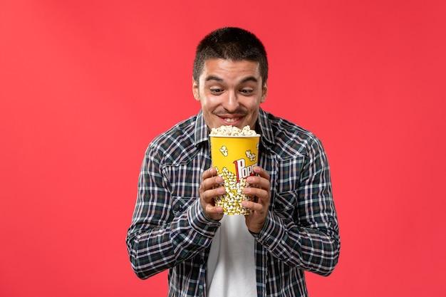 Widok z przodu młody mężczyzna trzyma popcorn na jasnoczerwonej ścianie kino kino teatralny mężczyzna