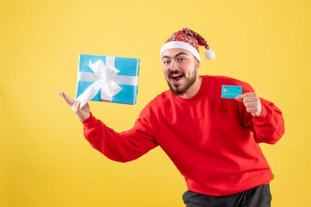 Widok z przodu młody mężczyzna trzyma prezent świąteczny i kartę bankową na żółtym tle