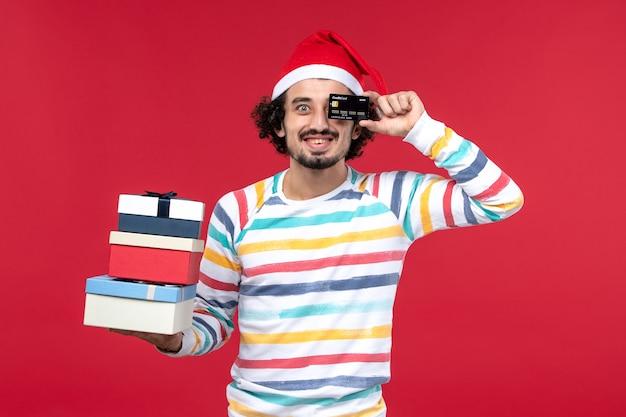 Widok z przodu młody mężczyzna trzyma prezenty i karty bankowe na czerwonej ścianie nowy rok pieniądze na czerwono