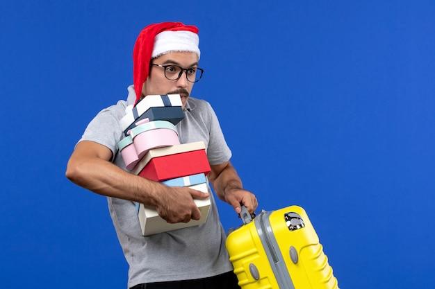 Widok z przodu młody mężczyzna trzyma prezenty i torbę na niebieskim tle lotu samolotem wakacje