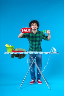 Widok z przodu młody mężczyzna trzyma sprzedaż pisanie i karta bankowa na niebieskim tle dom pieniądze mycie czyste zakupy prace domowe pralnia