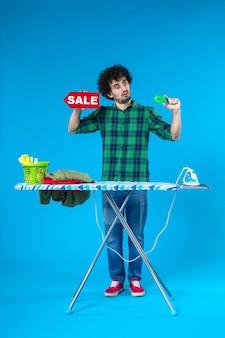 Widok z przodu młody mężczyzna trzyma sprzedaż pisanie i karta bankowa na niebieskim tle dom pieniądze pralka czyste zakupy prace domowe pralnia