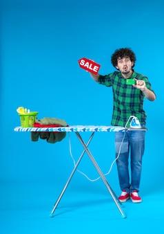 Widok z przodu młody mężczyzna trzyma sprzedaż pisanie i karta bankowa na niebieskim tle dom pieniądze pralka zakupy prace domowe czyste