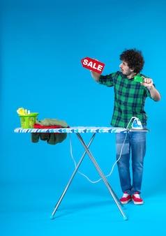 Widok z przodu młody mężczyzna trzyma sprzedaż pisanie i karta bankowa na niebieskim tle dom pieniądze pralka zakupy prace domowe pralnia
