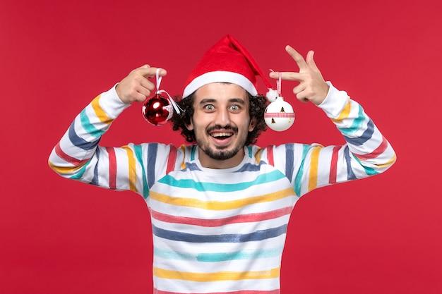 Widok z przodu młody mężczyzna trzyma zabawkę choinkową na czerwonej ścianie nowy rok czerwony wakacje