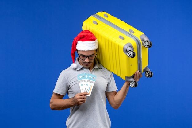 Widok z przodu młody mężczyzna trzymający ciężką torbę i bilety na niebieskiej ścianie loty samolotami wakacyjnymi