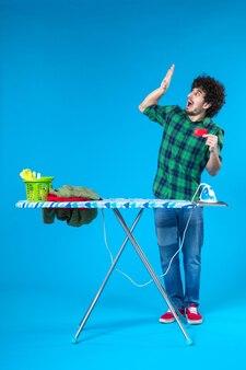Widok z przodu młody mężczyzna trzymający kartę bankową na niebieskim tle czyste pranie dom pieniądze mycie prace domowe zakupy żelazko