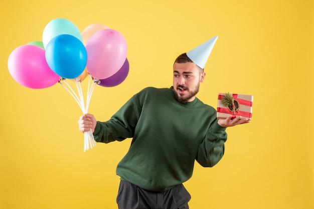 Widok z przodu młody mężczyzna trzymający kolorowe balony i obecny na żółtym tle