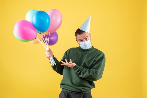Widok z przodu młody mężczyzna trzymający kolorowe balony na żółtym biurku