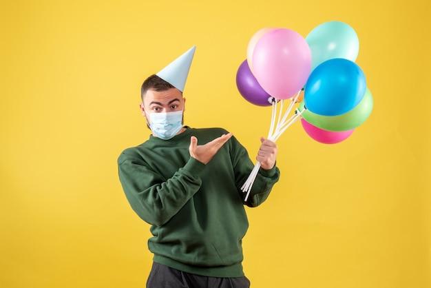Widok z przodu młody mężczyzna trzymający kolorowe balony w masce na żółtym tle