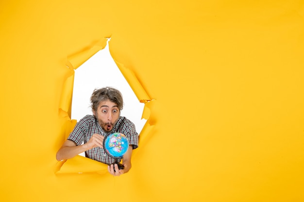Widok z przodu młody mężczyzna trzymający kulę ziemską na żółtym tle kolor planeta świąteczna wakacje światowe emocje