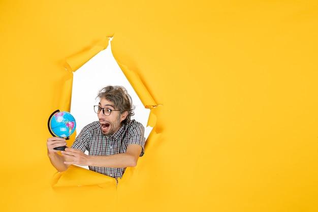 Widok z przodu młody mężczyzna trzymający kulę ziemską na żółtym tle kraj świata emocje święta kolor planety wakacje