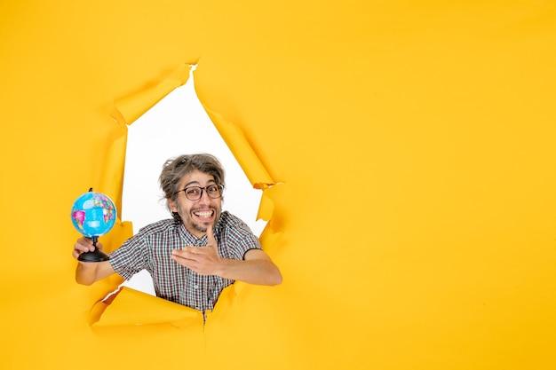 Widok z przodu młody mężczyzna trzymający kulę ziemską na żółtym tle kraj świata emocje wakacje święta kolor planety