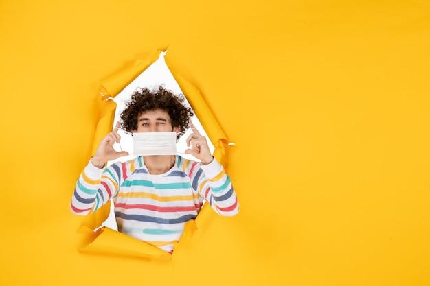 Widok z przodu młody mężczyzna trzymający maskę na żółtych zdrowych koronawirusach ludzkich kolorach pandemicznych zdjęć