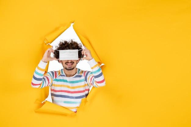 Widok z przodu młody mężczyzna trzymający maskę na żółtym zdjęciu zdrowie covid koronawirusy ludzkie pandemiczne kolory