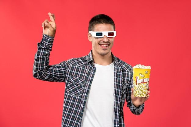 Widok z przodu młody mężczyzna trzymający pakiet popcornu i noszący okulary przeciwsłoneczne -d na jasnoczerwonej ścianie kino kino film