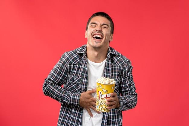 Widok z przodu młody mężczyzna trzymający pakiet popcornu i śmiejący się na jasnoczerwonej ścianie kino film teatralny mężczyzna