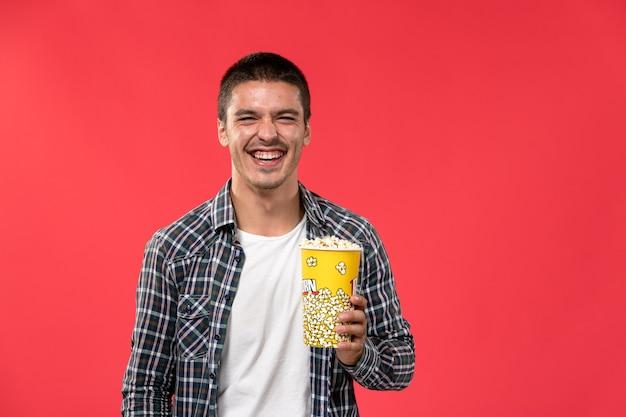 Widok z przodu młody mężczyzna trzymający popcorn i śmiejąc się na jasnoczerwonej ścianie męski film kino kino