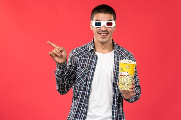 Widok z przodu młody mężczyzna trzymający popcorn in -d okulary na jasnoczerwonej ścianie męski film kinowy